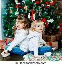 girls with Christmas tree - two sisters sitting on the floor...