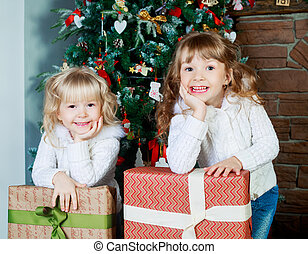 sisters with Christmas tree - two sisters at home with the...