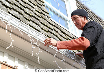 installing of the outside Christmas lights - a man hanging...
