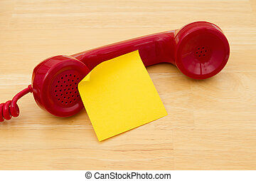 A retro red phone with yellow sticky note