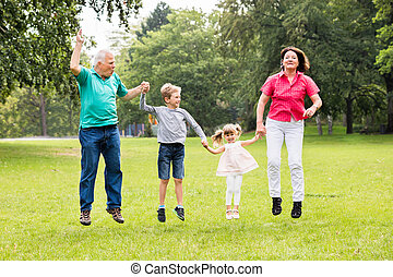 Grandparents And Grandchildren Jumping Together In Park