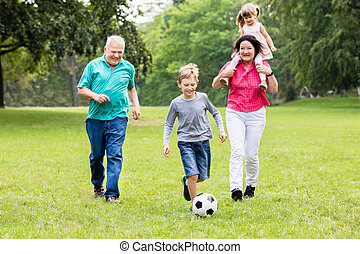 Grandparent And Grandchildren Playing Soccer Ball Together -...