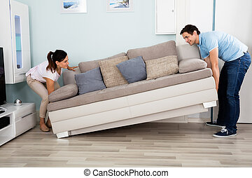 Couple Placing Sofa In Living Room - Young Happy Couple...