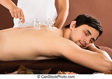 Person's Hand Giving Cupping Treatment To Man - Person's...