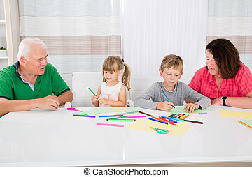 Multi Generation Family Drawing Together With Colorful Pencils