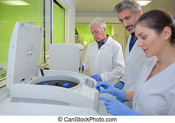 Three lab technicians using machinery