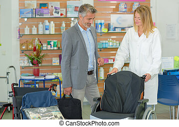 Man looking at wheelchair in medical supplies shop