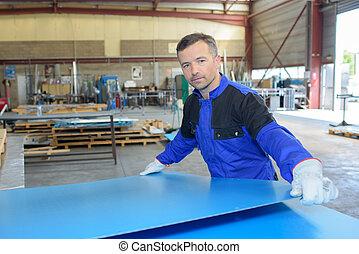 Workman moving sheet of metal