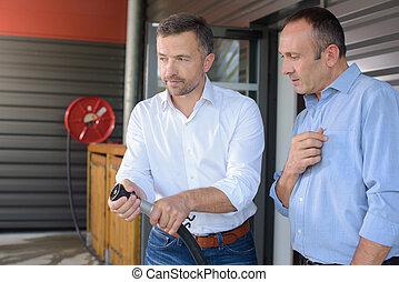 Two men turning on hose pipe