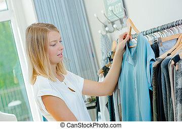 Young woman choosing a garment