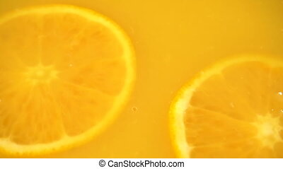 Sliced orange falling into orange juice in slow motion