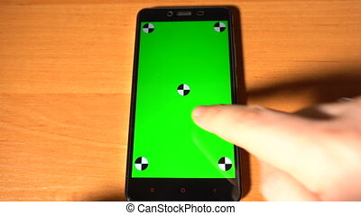 Smartphone with green screen chromakey on the table and mans...