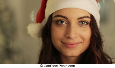 Close up woman in santa hat portrait posing on tree lights background. , christmas holiday concept, happy and emotions