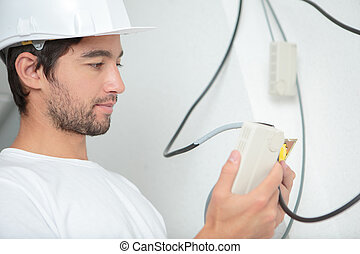 Electrician holding suspended switch