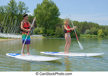 couple standing on paddle board