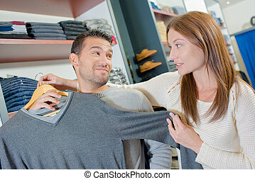 Couple in clothes shop, lady holding jumper against man