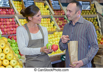 Man buying apples in greengrocers