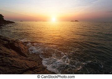 Sunset at rocky sea coast.