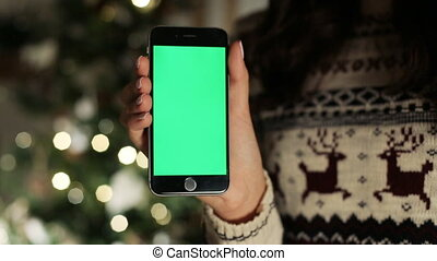 NEW YORK - January 17, 2015: Close-up of female hands touching of smartphone. Green screen Chroma Key. Close up. Tracking motion. with blur christmas decoration background