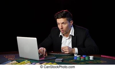 Man sitting at a laptop and playing at online casinos. Close up