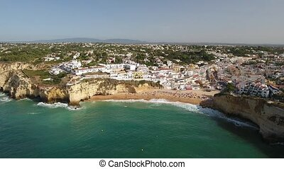 Aerial. Flying over the beach and the tourist village of...