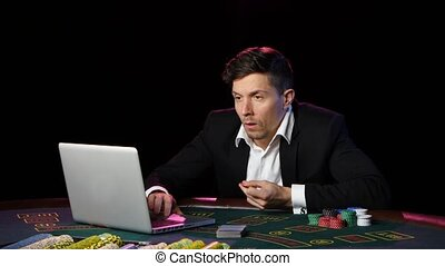 Online poker players and wins. Close up - A man in a suit...