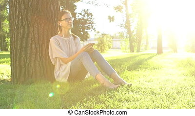 Young woman listening to music and using smartphone in the park