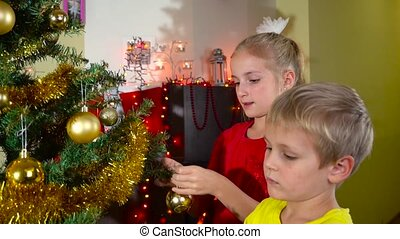 kids decorating christmas tree - girl and boy decorating...