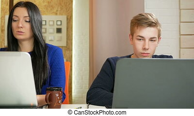 Attractive woman and a young man working in the office on laptops. Focused printed on the keyboard, and look at the screens. Moving the camera.