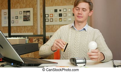 A man pays for the card purchase bulbs in the office using...