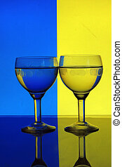 glass of water on blue yellow background