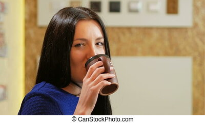 Attractive woman working at a laptop and drinking coffee from cups in the office. Long black hair and a blue dress. She looks into the camera and smiling