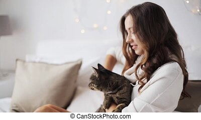 happy young woman with cat in bed at home - pets and people...