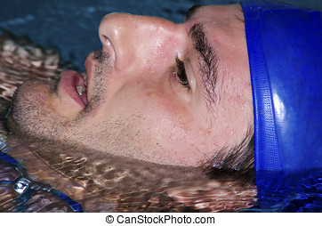 Young man swimming backstroke in a public pool