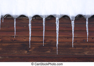 Icicles hang from the undulating roof. The wall of the...