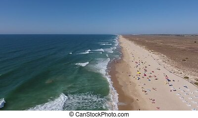 Aerial. Flying over Barril beach with tourists, from the sky...