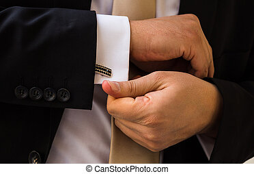 groom hands fixing his cull links before ceremony