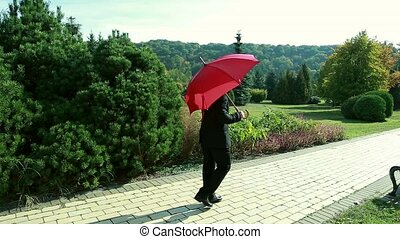 Mature man outdoors in autumn with a red umbrella.