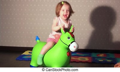 a child sits on a toy horse - a child jumping on an...
