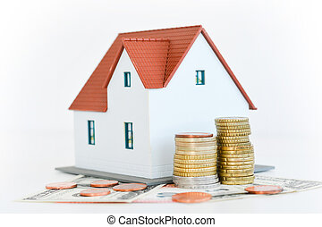 House ownership concept – a model house on a pile of coins