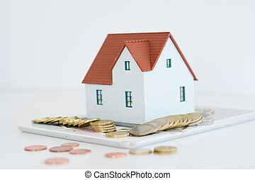 Digital tablet, coins and house model on white background