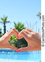 Hand painting a heart shape sun on sky
