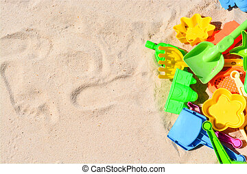 Many colorful beach toys in sand