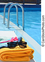 Sunglasses towel and a hat near a swimming pool on a hot summer day