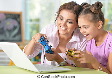 Mother and daughter playing videogames - Young mother and...