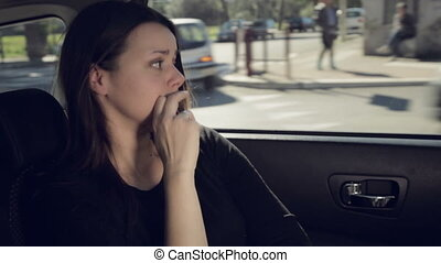 Sad woman sitting in car writing text message with cell phone crying
