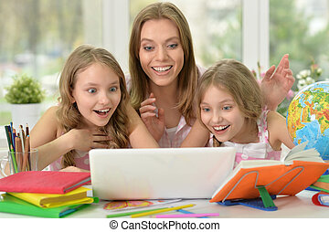 girls with mother on lesson with laptop - portrait of Cute...