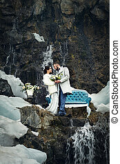 Happy couple hugging on rock on the background of nature