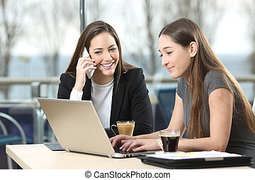 Two businesswomen working together in a bar - Two...