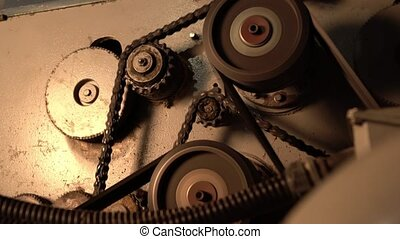 Close-up view of gears and chain rotate on machine -...